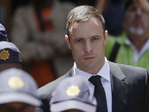 FILE - In this Friday, Oct. 17, 2014 file photo, Oscar Pistorius is escorted by police officers as he leaves the high court in Pretoria, South Africa. Prison officials have recommended that Pistorius be released from prison on Aug. 21 to go under house arrest. Acting National Commissioner of Correctional Services Zach Modise says that a prison committee recommended Pistorius be released  after serving one sixth of his five-year sentence, or 10 months, for shooting girlfriend Reeva Steenkamp. A decision by the parole board is pending. (AP Photo/Themba Hadebe, File)